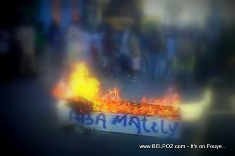 ABA MARTELLY - Protesters in Haiti burn a white coffin with slogan