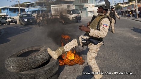 Haitian Police kicking a burning tire during a street protest
